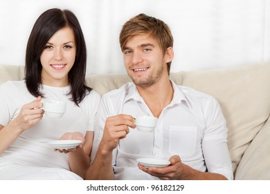 beautiful young couple drink coffee hold cup, sitting on a sofa happy smile looking at camera, portrait of lovely young man and woman on the couch