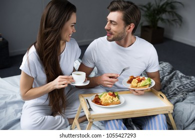 Beautiful young couple drinking coffee and eating breakfast in bed