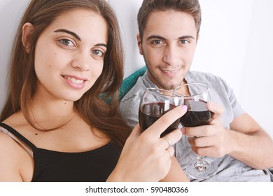 Beautiful young couple drinking wine in bed. Indoors.