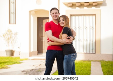 Beautiful young couple embracing each other and excited about the house they just bought
