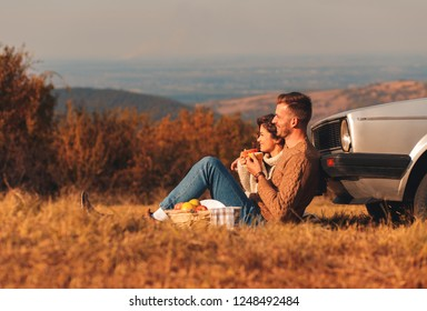 Beautiful young couple enjoying picnic time on the sunset. They drinking tea and sitting in a meadow leaning against a old fashioned car.