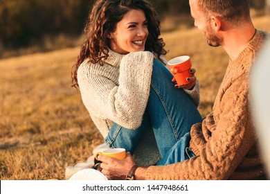 Beautiful young couple enjoying picnic time on the sunset. They drinking tea and sitting in a meadow leaning on old fashioned car.
