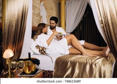 Beautiful young couple enjoying and relaxing in gorgeous hotel bedroom