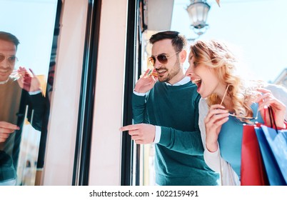 Beautiful young couple enjoying in shopping, having fun together in the city. Consumerism, love, dating, lifestyle concept