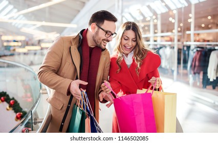 Beautiful young couple enjoying in shopping, having fun together in shopping mall. Consumerism, love, dating, lifestyle concept