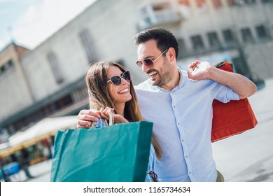 Beautiful young couple enjoying in shopping, having fun in the city