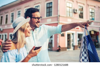 Beautiful young couple enjoying in shopping, having fun in the city. Consumerism, love, dating, lifestyle concept