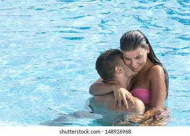 Beautiful young couple enjoying in swimming pool on a hot summer day