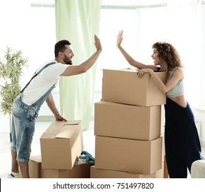 """beautiful young couple giving a """"high five"""" in a new house"""