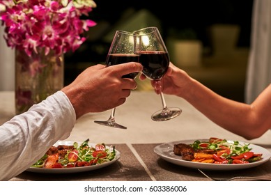 Beautiful young couple with glasses of red wine in luxury restaurant.