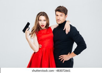 Beautiful young couple with gun standing and hugging