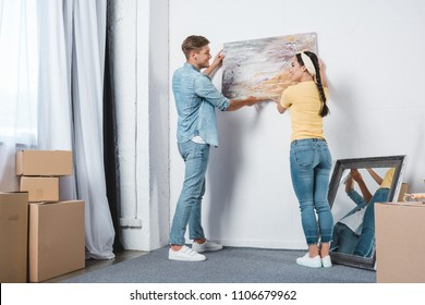 beautiful young couple hanging picture on wall together while moving into new home