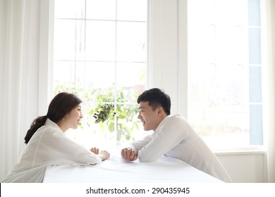 beautiful young couple having a conversation while looking at each other over a window background in a bright room
