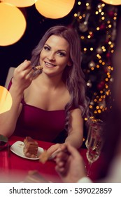 Beautiful young couple having a conversation on a romantic Christmas dinner, drinking wine and eating cake