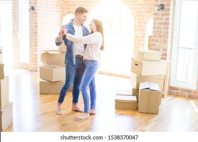 Beautiful young couple having fun dancing at new apartment, celebrating moving to a new home