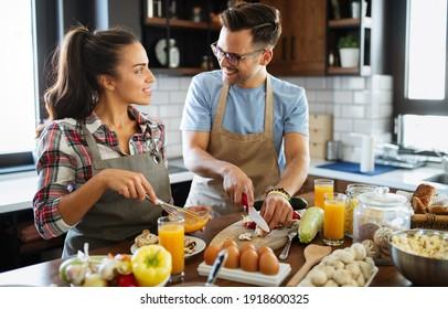 Beau jeune couple s'amusant dans la cuisine en cuisinant.