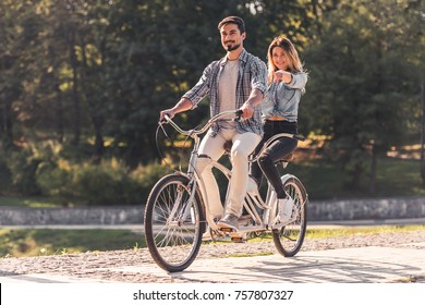 Beautiful young couple is having fun while riding a tandem bicycle in the park