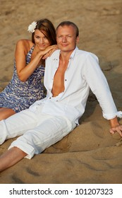Beautiful young couple having rest on river beach