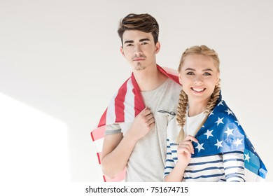 beautiful young couple holding american flag and smiling at camera on grey