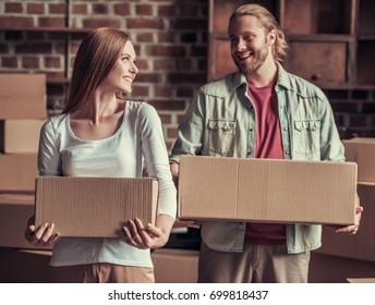 Beautiful young couple is holding cardboard boxes, looking at each other and smiling while moving into new apartment