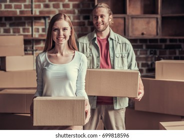 Beautiful young couple is holding cardboard boxes, looking at camera and smiling while moving into new apartment