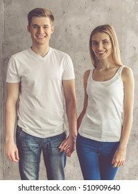 Beautiful young couple is holding hands, looking at camera and smiling, on concrete wall background