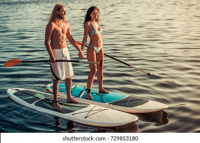 Beautiful young couple is holding hands and smiling while SUP surfing