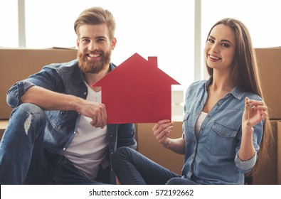 Beautiful young couple is holding a paper house and a key, looking at camera and smiling while sitting among moving cardboard boxes
