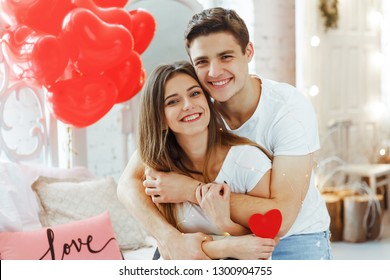 Beautiful young couple at home. Hugging, kissing and enjoying spending time together while celebrating Saint Valentine's Day with air balloons in shape of heart on the background.