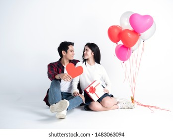 Beautiful young couple at home. Hugging, kissing and enjoying spending time together while celebrating Saint Valentine's Day with gift box in hand and air balloons in shape of heart on the background