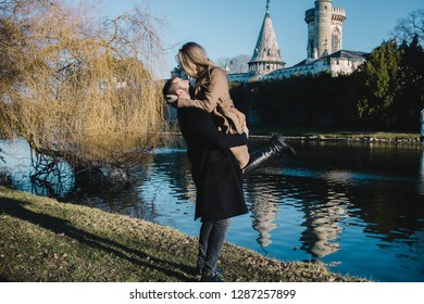Beautiful and young couple hugging behind the lake. Blonde woman and bearded man in winter coat posing for camera