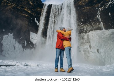 beautiful young couple hugging and kissing near majestic skogafoss waterfall in iceland