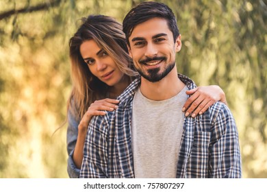 Beautiful young couple is hugging, looking at camera and smiling while resting in the park