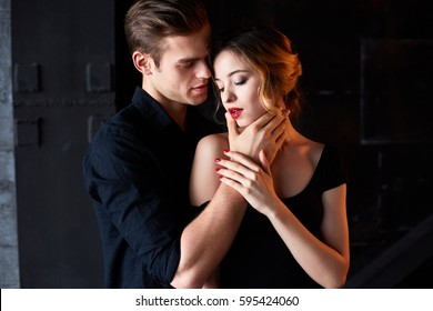 Beautiful young couple hugging on a black background