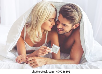 Beautiful young couple is hugging and smiling while lying covered with blanket in bed. Woman is holding a condom