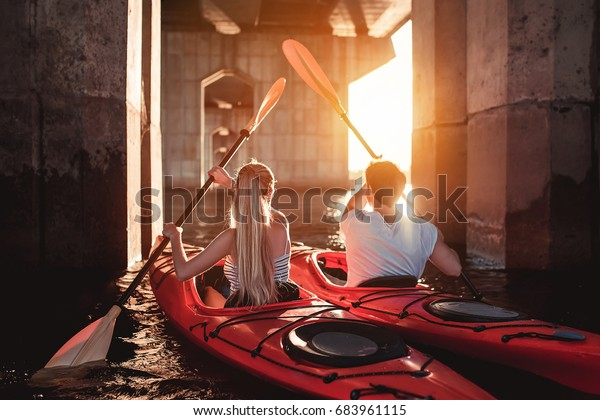 Beautiful young couple is kayaking on river. Waiting for the sunset.