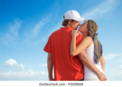 Beautiful young couple kissing against blue sky