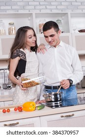 Beautiful young couple in the kitchen, fun and happy because the man and woman