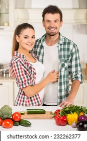Beautiful young couple in the kitchen while cooking.