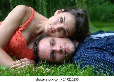 Beautiful young couple laying on the ground with the woman's head resting on the mans in a garden setting