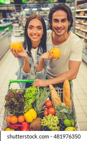 Beautiful young couple is leaning on the shopping cart, looking at camera and smiling while choosing food in the supermarket. Girl is holding oranges