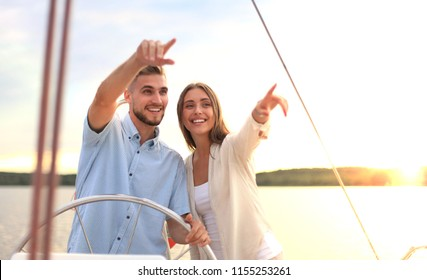 beautiful young couple looking away while standing together on yacht.