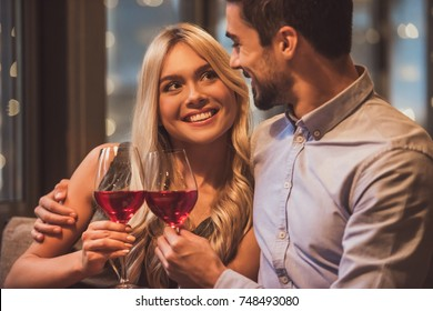 Beautiful young couple is looking at each other, drinking wine and smiling during their date in a restaurant