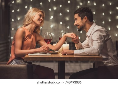 Beautiful young couple is looking at each other and smiling during their date in a restaurant, man is holding his girlfriend's hand