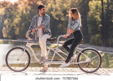 Beautiful young couple looking at each other and smiling while riding a tandem bicycle in the park