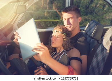 Beautiful young couple looking at a tablet in a car by sunset.