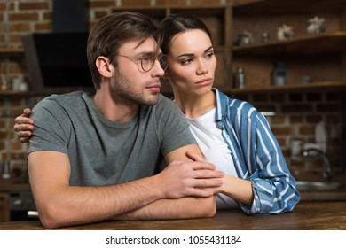 Beautiful young couple in loungewear sitting by table in kitchen