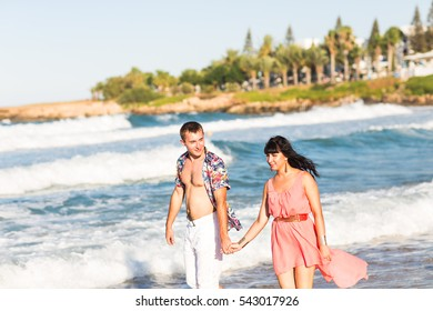 Beautiful young couple in love enjoying and having fun at the beach.
