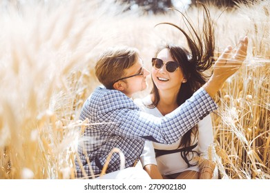 beautiful young couple in love girl and man in sunglasses and bright clothing embracing and kissing in wheat field