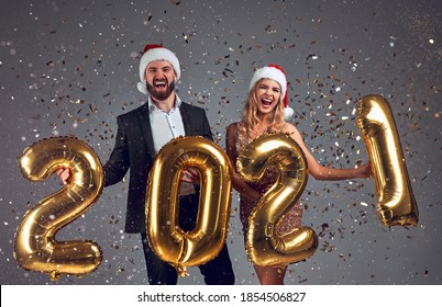 Beautiful young couple in love, having fun at a New Year's Eve Party, wearing Santa's hats and holding a gold balloons number 2021. Isolated grey background with confetti.